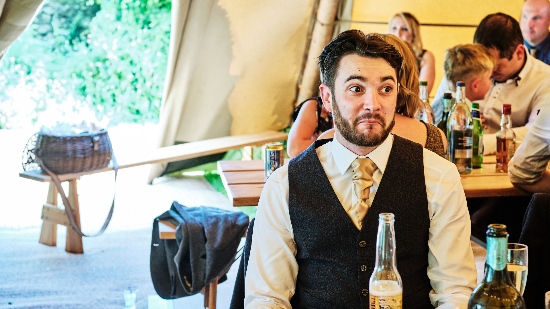 colour photograph of a wedding guest smiling during the speeches at a wedding