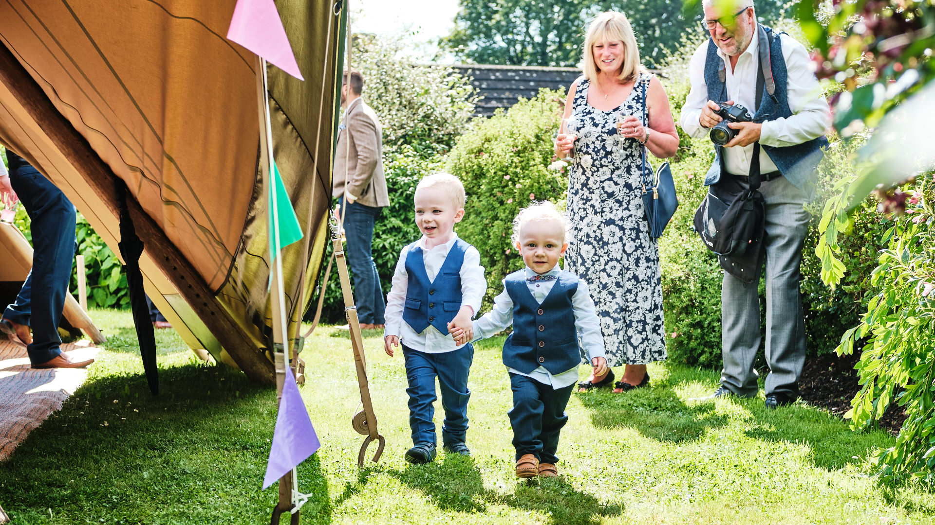 colour photograph of two small boys dressed in suits walking hand in had at a wedding