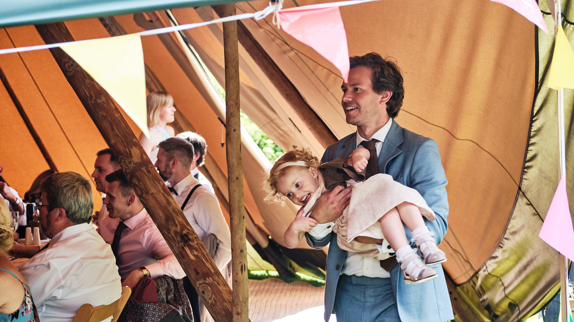 colour photograph of a wedding guest carrying his young daughter during a wedding reception