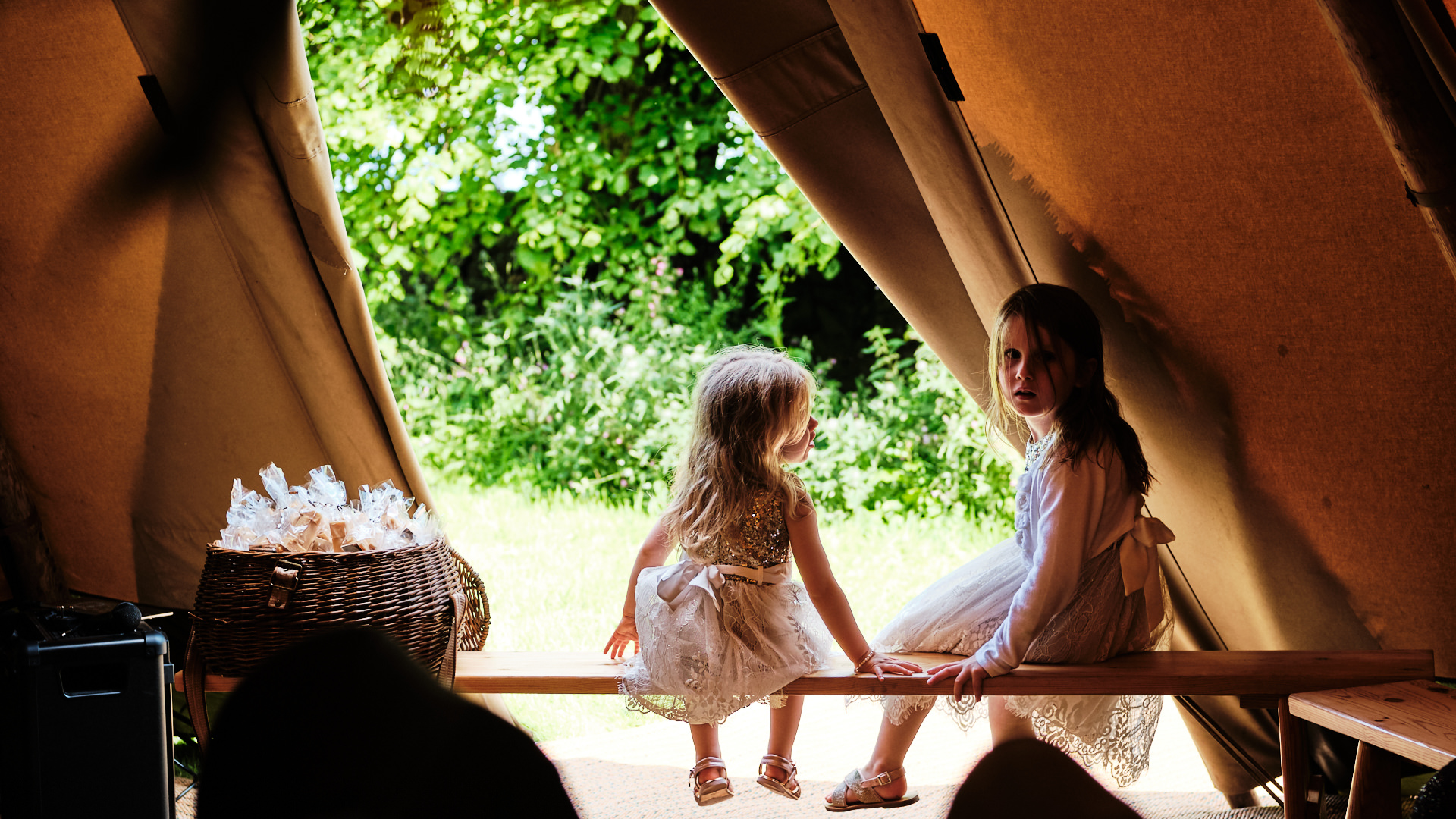 colour photograph of a two young flower girls sitting together during a wedding reception
