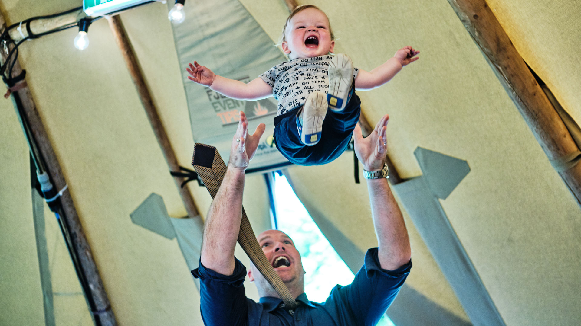 colour photograph of a wedding guest throwing his baby son in the air during a wedding reception