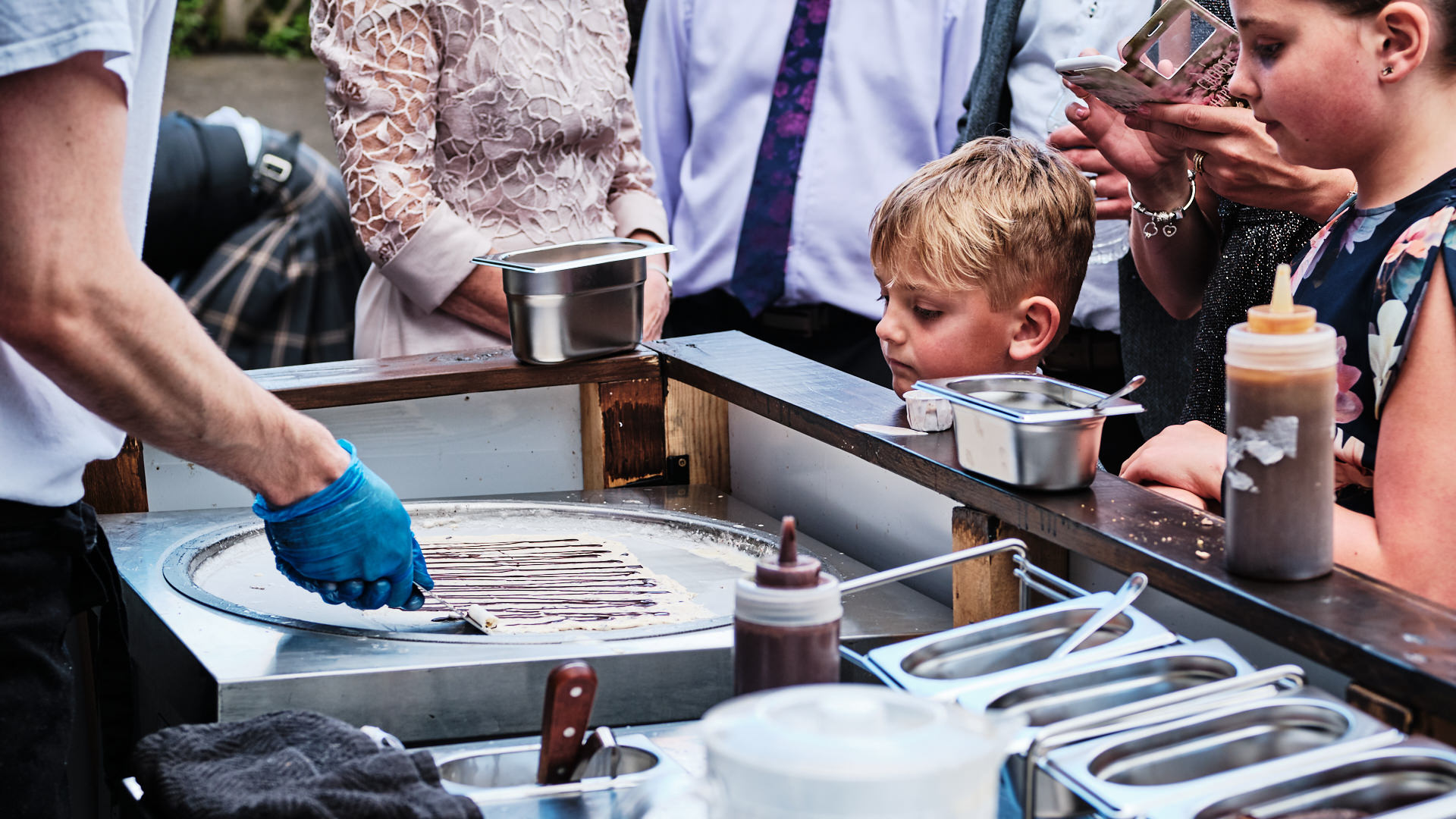 colour photograph of children watching a chef make crepes as apart of a wedding breakfast