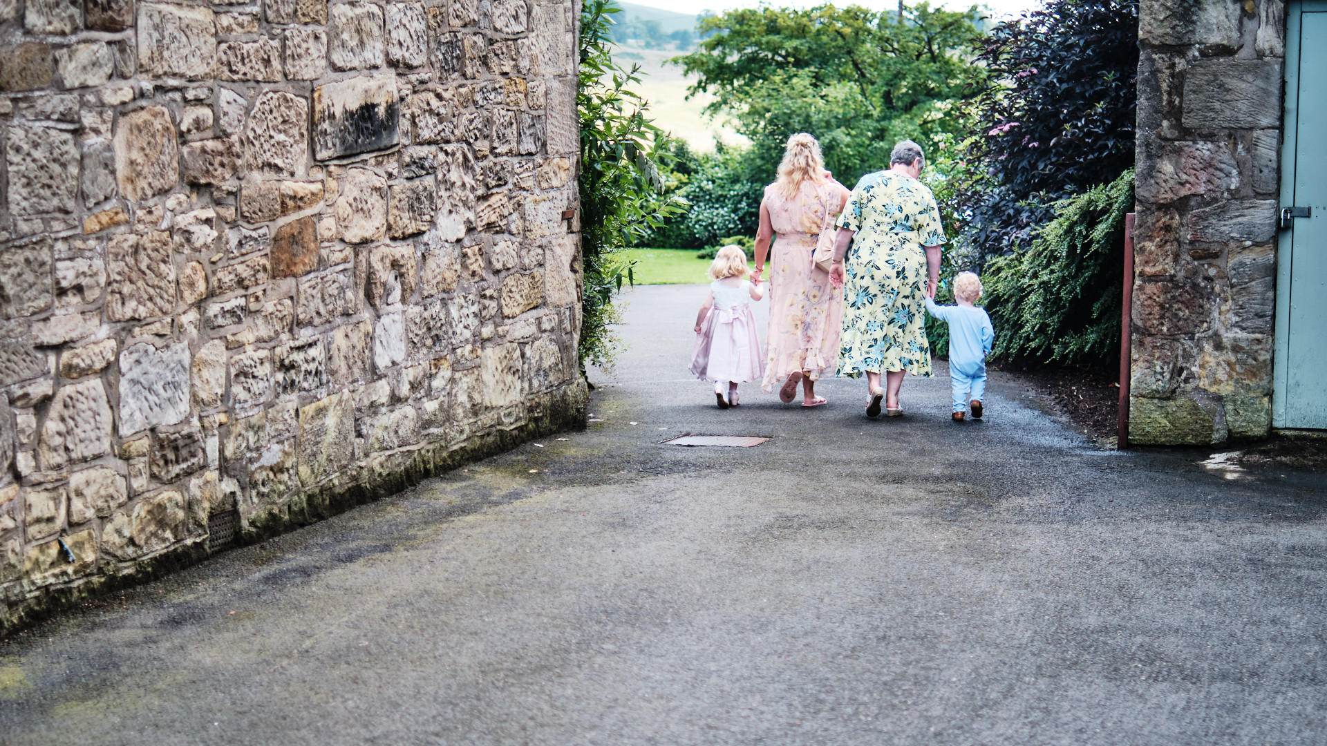 colour photograph of wedding guests photographer from behind while walking hand in hand with small children