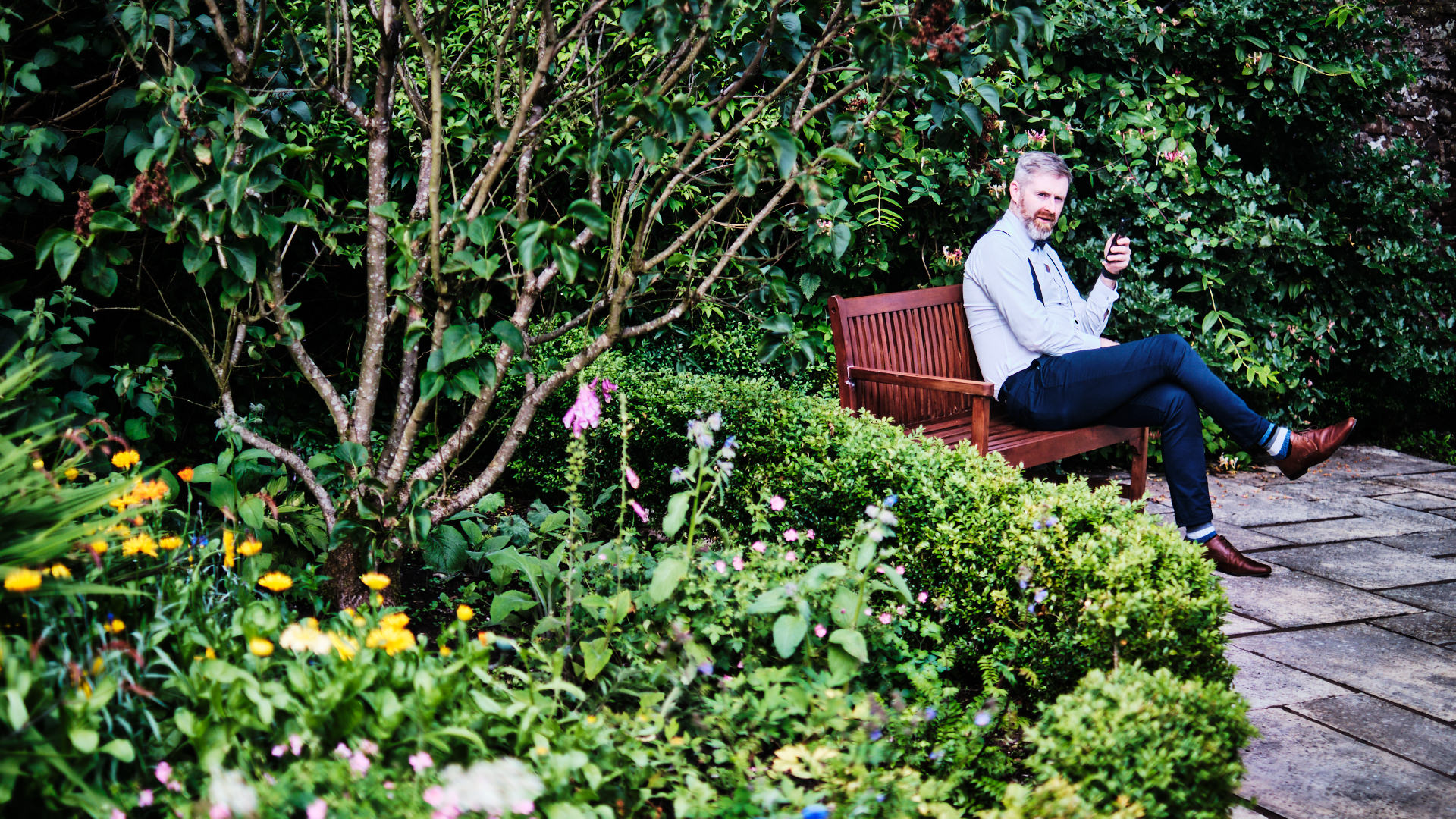 colour photograph of a wedding guest smoking a pipe in the garden of the wedding venue