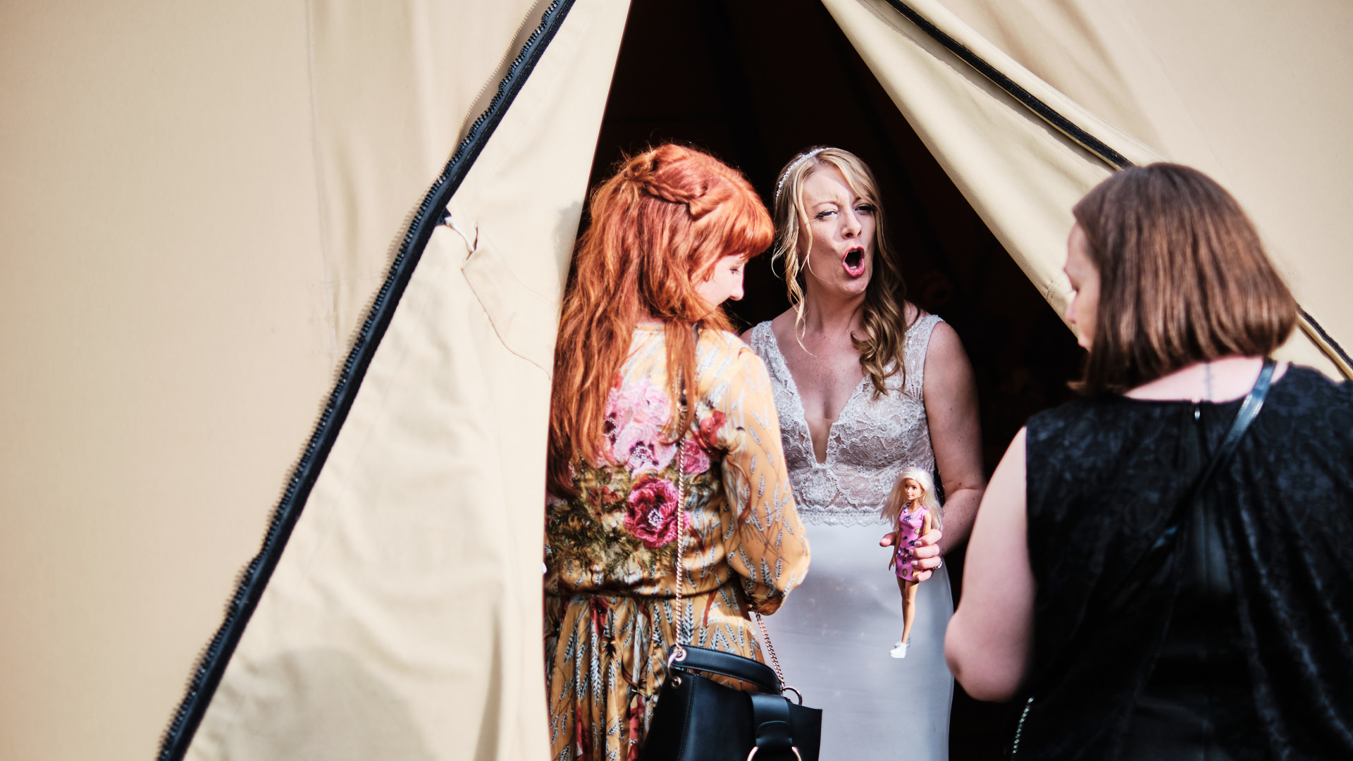 colour photograph of a bride holding a barbie doll and chatting to her guests during her wedding reception