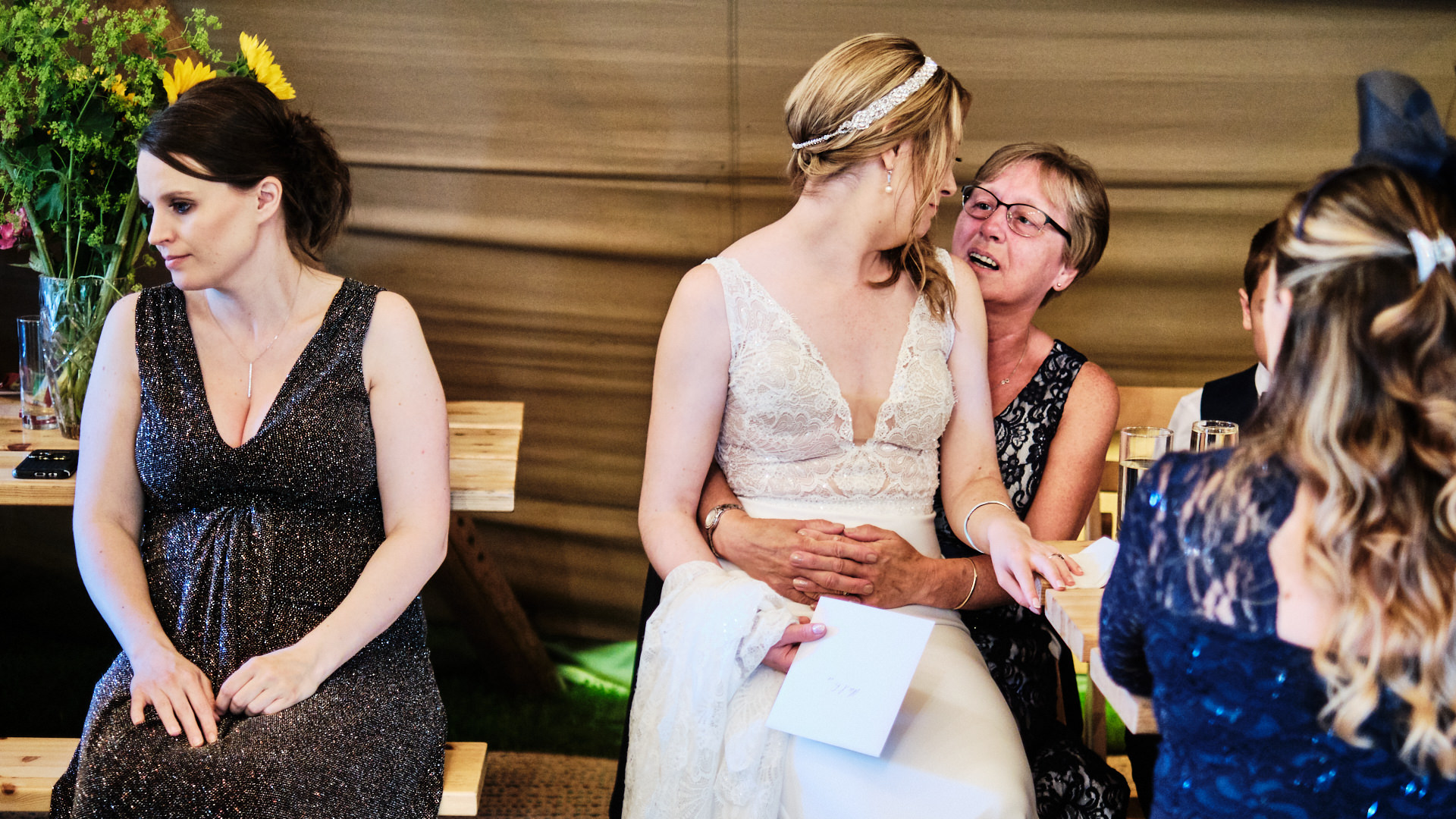 colour photograph of a bride sitting open a female wedding guest's knee during her wedding reception