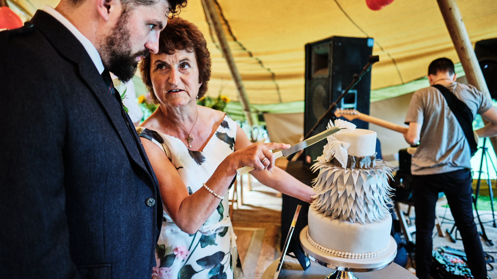 colour photograph of the bride groom and his mum arranging the wedding cake just before the official cake cutting at his wedding