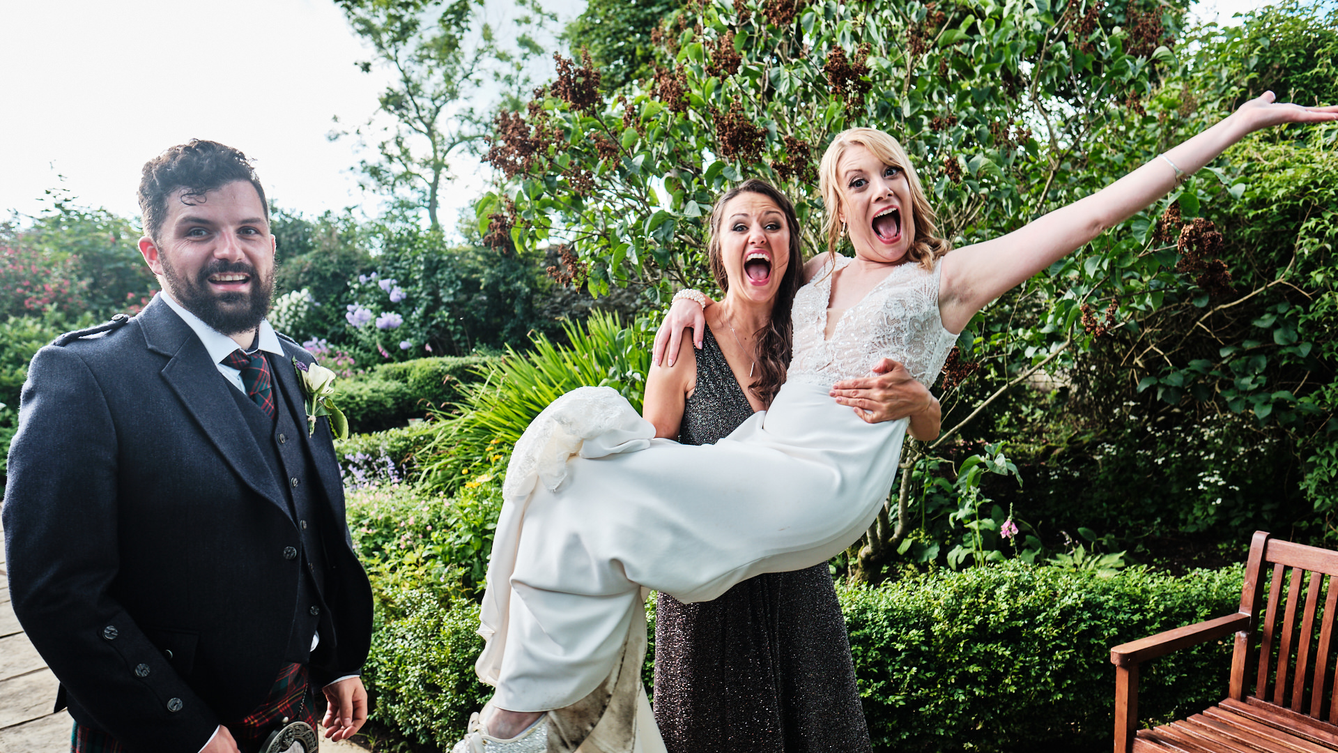 colour photograph of a bride being carried by her bridesmaid during the wedding reception while the groom laughs