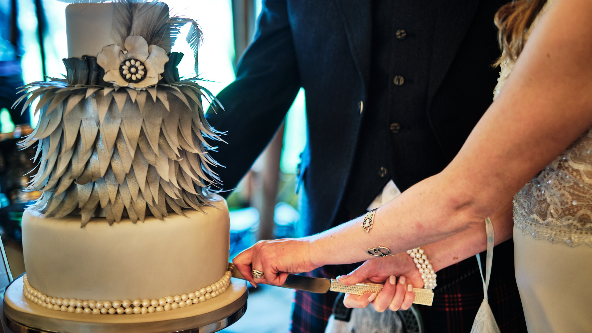 colour photograph of a bride and groom's hands as they cut their wedding cake