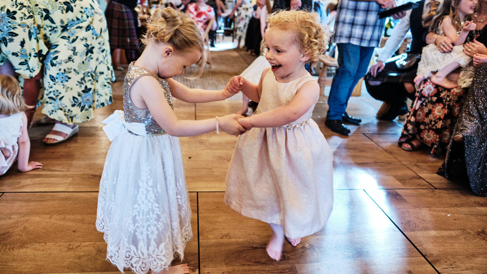 colour photograph of two small girls dancing at a wedding