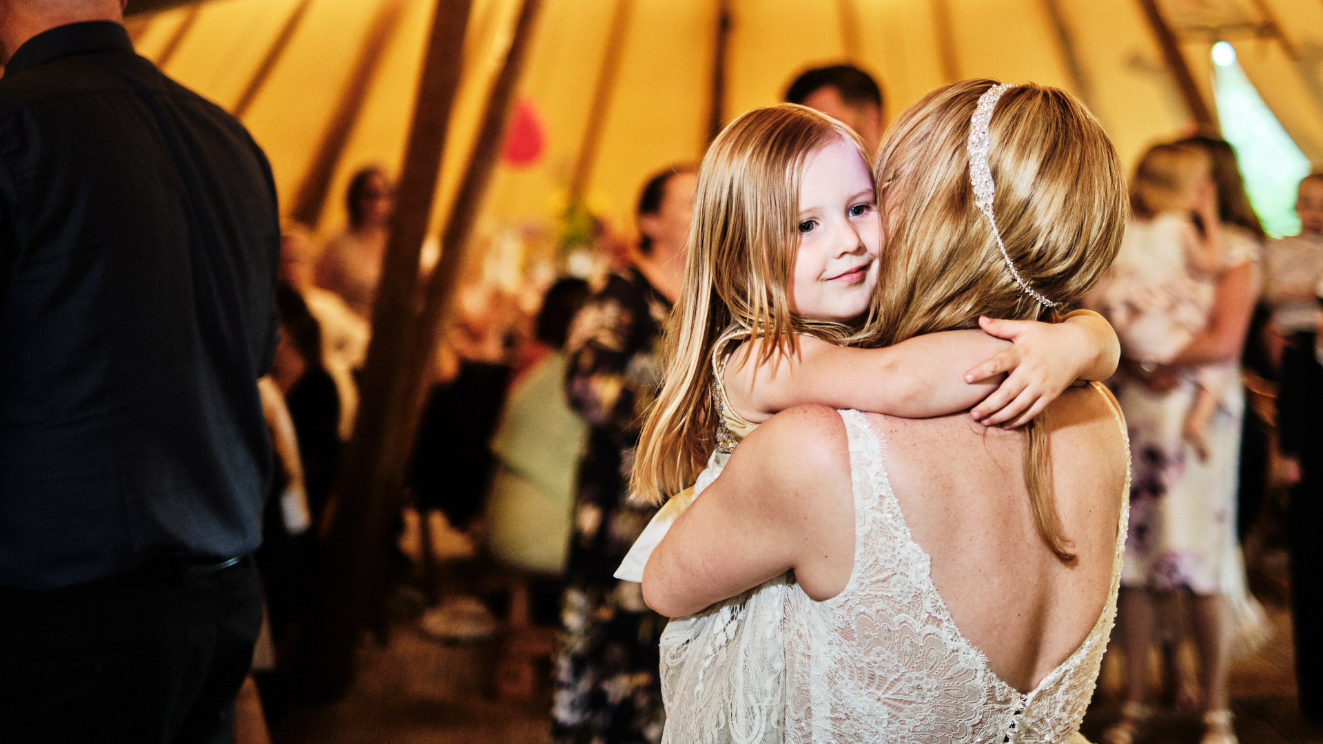 colour photograph of the bride carrying and dancing with a young girl at her wedding