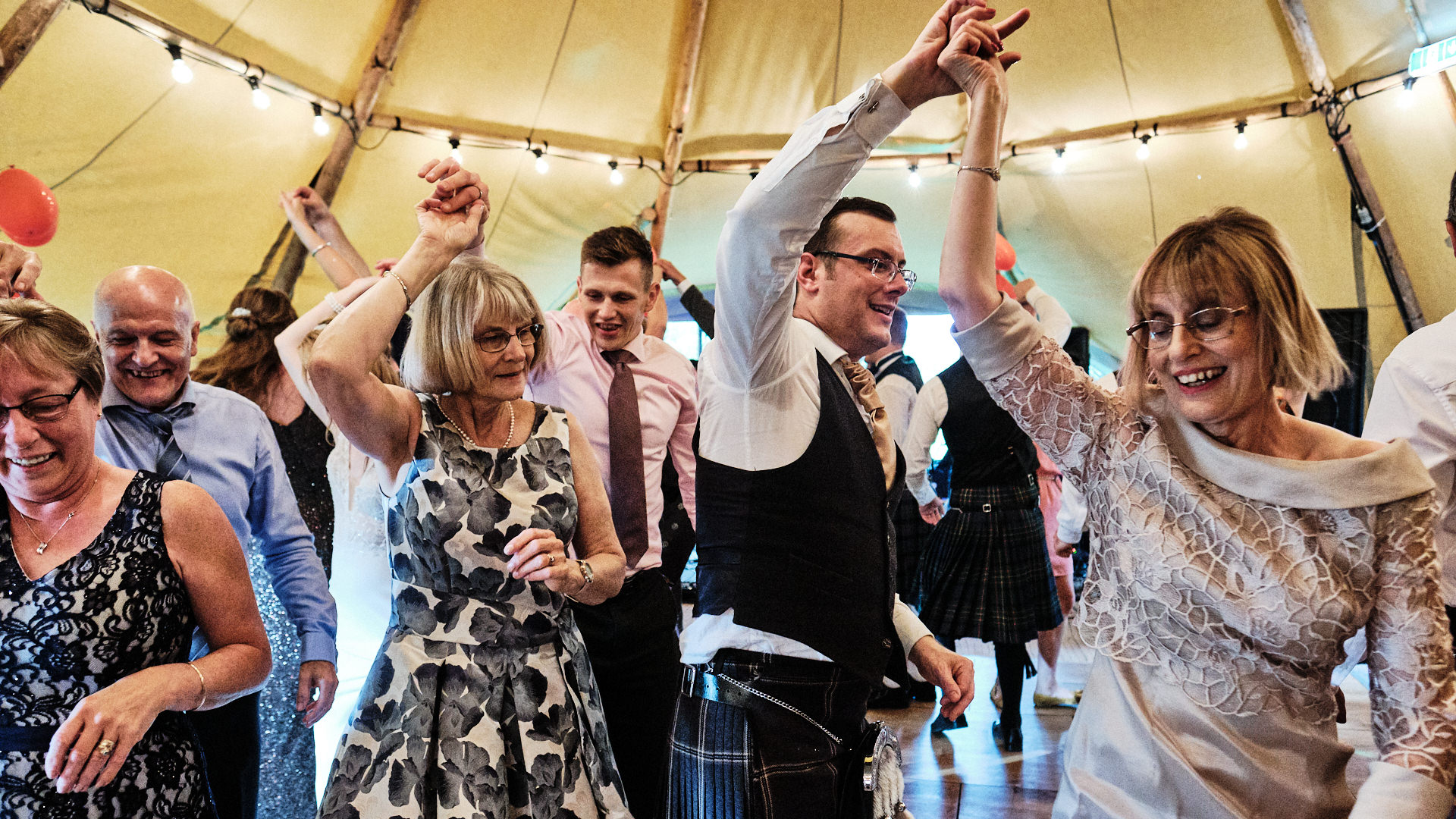 colour photograph of wedding guests dancing during a ceilidh at a wedding