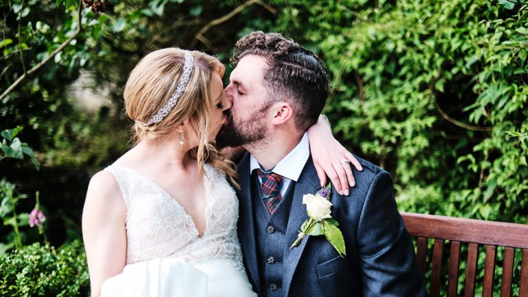 colour photograph of a bride and groom kissing in their garden